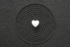 在黑沙子的白色心脏 免版税库存照片