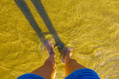 在黄沙海滩的女性腿 免版税库存图片