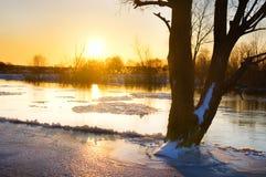 在冻河的日落在冬天 免版税库存照片