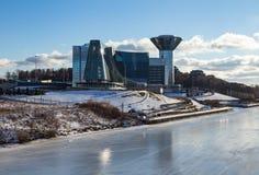 在冻河的河岸的令人惊讶的被反映的大厦在一个晴天 免版税库存照片