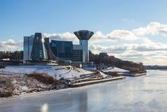 在冻河的河岸的令人惊讶的被反映的大厦在一个晴天 库存照片