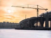 在冻河的被定调子的图象建设中路桥梁有反对多云天空机智的背景的一架大塔吊的 免版税库存照片