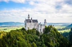 在巴法力亚阿尔卑斯紧贴的新天鹅堡城堡 库存图片