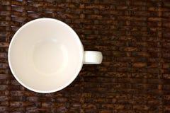 在织法木头桌上的白色杯子 免版税库存图片