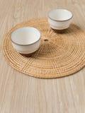 在织法盘子木头地板上的茶杯日本式 免版税图库摄影