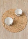 在织法盘子木头地板上的茶杯日本式 免版税库存照片
