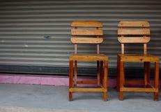 在水泥地板上的两把木椅子与路辗在后边的快门门 库存图片
