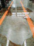 在水泥地板上的油或水泄漏,需要干净和仔细的丹 库存照片