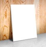 在水泥地板和木墙壁, Canv的空白的白色海报框架 免版税库存照片