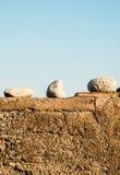 在水泥墙壁上的三块白色石头有蓝天的 免版税库存照片