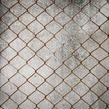 在水泥墙壁上的生锈的铁链子铁丝网 库存照片