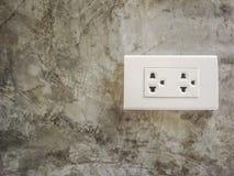 在水泥墙壁上的白色插座插口 免版税库存图片