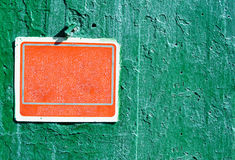 在水泥墙壁上的红色生锈的脏的老塑料标志 图库摄影