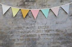 在水泥墙壁纹理的五颜六色的党旗子 免版税库存图片