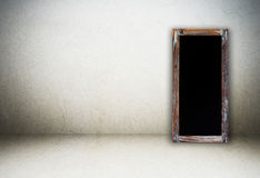 在水泥墙壁背景的空白的葡萄酒粉笔板 库存图片