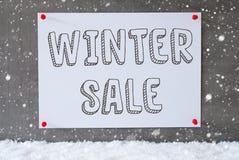 在水泥墙壁,雪花,文本冬天销售上的标签 图库摄影