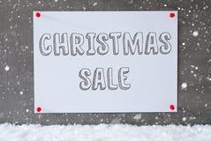 在水泥墙壁,雪花,文本圣诞节销售上的标签 免版税库存照片