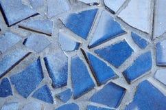 在水泥的蓝色破裂的瓦片 免版税库存图片