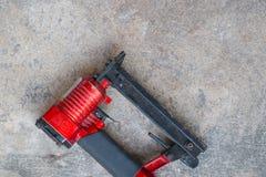 在水泥背景,喷枪handpiece的气动力学的钉书针  免版税库存图片