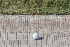 在水泥路的高尔夫球,在绿色高尔夫球场外面 图库摄影