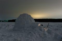 在冻海的雪园屋顶的小屋在晚上 免版税库存图片