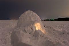 在冻海的雪园屋顶的小屋在晚上 库存照片