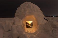 在冻海的雪园屋顶的小屋夜的背景的 库存照片