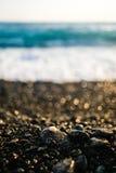 在黑海滩的小小卵石与轻美好的晚上有理想的bokeh背景 免版税图库摄影