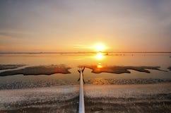 在洗涤出海口泥滩的日落处于低潮中 库存图片