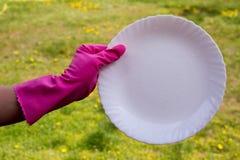 在洗涤板材的桃红色防护手套的手 免版税库存照片