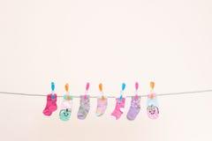 在洗涤的线风景的七只婴孩袜子 免版税库存照片