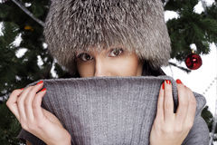 在戴温暖的帽子的新年树附近的少妇 免版税库存图片