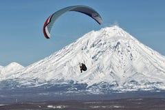 在活火山背景的滑翔伞飞行  图库摄影