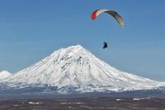 在活火山背景的滑翔伞飞行  库存图片