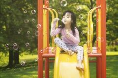在幻灯片的女孩吹的肥皂泡 免版税图库摄影