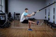 在锻炼期间的可爱的人与在健身房的停止皮带 免版税库存图片