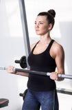 在锻炼期间的美丽的浅黑肤色的男人在健身房 免版税库存图片