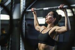 在锻炼期间,强有力的可爱的妇女CrossFit教练员做引体向上 免版税库存照片