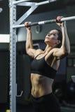 在锻炼期间,强有力的可爱的妇女CrossFit教练员做引体向上 库存照片
