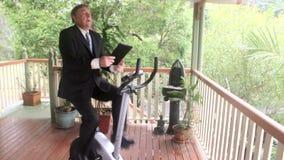 在锻炼脚踏车的商人 影视素材