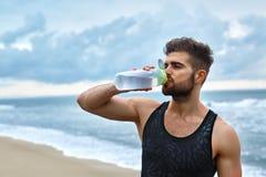 在锻炼以后的人饮用的刷新的水在海滩 饮料 库存图片
