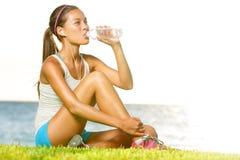 在锻炼以后的健身妇女饮用水外面 免版税库存图片