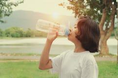 在锻炼以后的女孩饮用水 库存照片