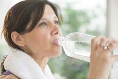 在锻炼以后的妇女饮用水 库存图片