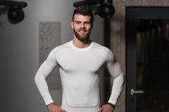 在锻炼以后的英俊的人在健身房 库存照片