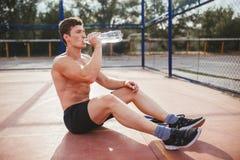 在锻炼以后的运动员饮用水 免版税图库摄影