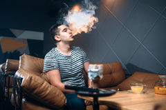 年轻在水烟筒酒吧的人抽烟和放松 免版税库存照片