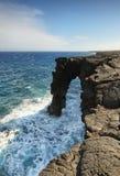 在黑熔岩岩石峭壁的自然曲拱 免版税图库摄影