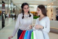 在购物中心的两逗人喜爱的女孩步行与礼物请求看入 从什么的惊奇他看见了 库存照片