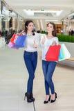 在购物中心的两逗人喜爱的女孩步行与礼物请求,显示翘拇指 免版税库存图片